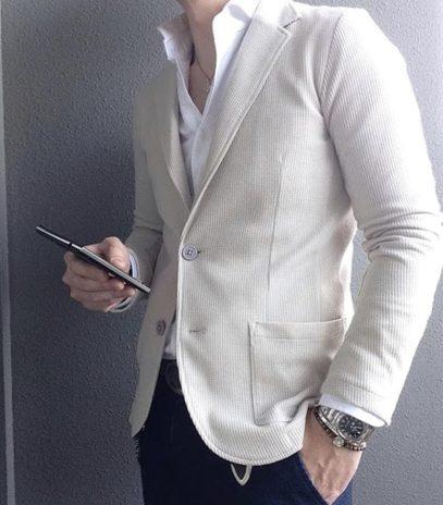ニットのベージュジャケットにデニムスラックスを合わせたスタイリング